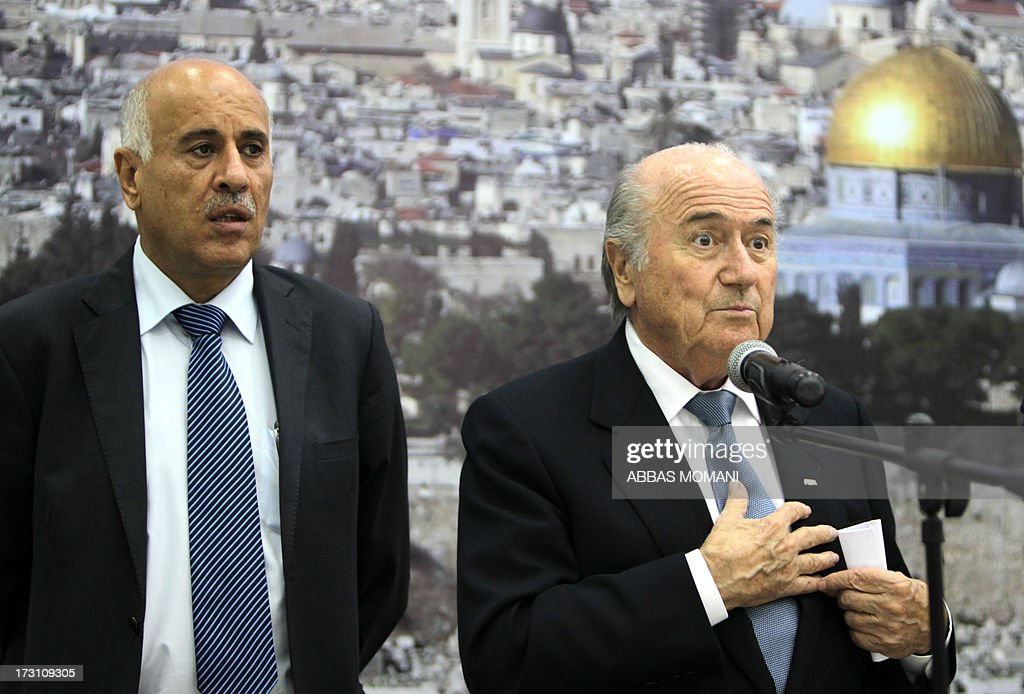 President Sepp Blatter (R) speaks as Palestinian Football Association chairman Jibril Rajoub listens on during a press conference in the West Bank city of Ramallah on July 7, 2013. Blatter is on a four-day-official visit to the Palestinian territories and Israel and neighboring Jordan during which he will notably launch football turf fields.