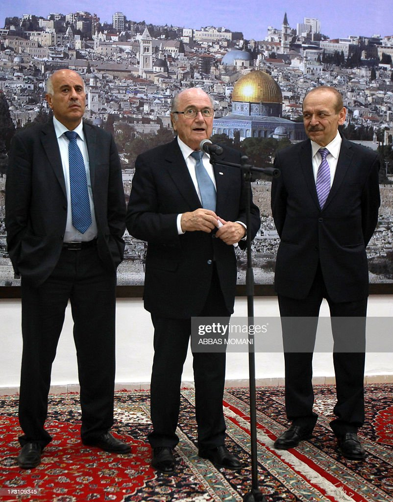 President Sepp Blatter (C) speaks as President of the Palestinian Football Federation Jibril Rajoub (L) and Yasser Abed Rabbo (R), Palestinian politician and a member of the Palestine Liberation Organization's Executive Committee, listen on, in the West Bank city of Ramallah, on July 7, 2013. Blatter is on a four-day-official visit to the Palestinian territories and Israel and neighboring Jordan during which he will notably launch football turf fields.