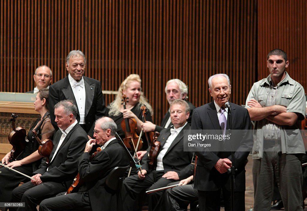 President Shimon Peres speaking to the audience with smiling conductor Zubin Mehta and musicians, members of the Israel Philharmonic Orchestra listening in the Mann Auditorium, Tel Aviv, Israel, October 16, 2010.