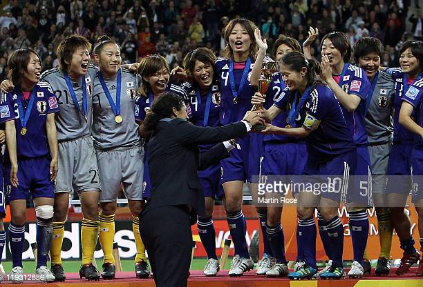 President Steffi Jones hands over the trophy to Homara Sawa of Japan after the FIFA Women's World Cup Final match between Japan and USA at the FIFA...