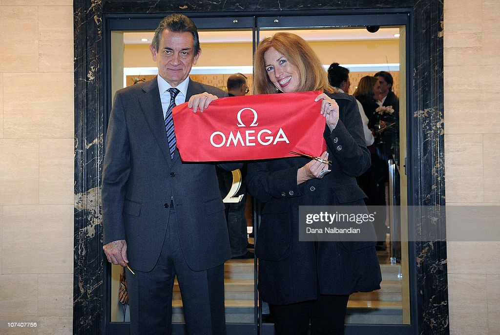 President Stephen Urquhart and Seattle Art Museum Vice Director Maryann Jordan display the cut ribbon at the opening party at OMEGA Boutique on...