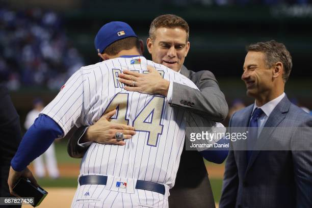 President Theo Epstein of the Chicago Cubs hugs Anthiny Rizzo as general manager Jed Hoyer smiles during a World Series Championship ring ceremony...