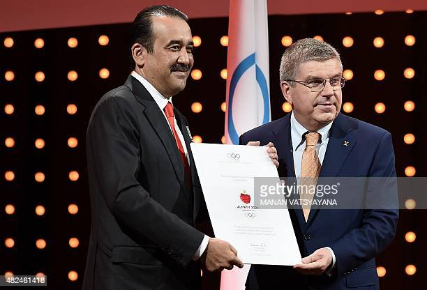 IOC president Thomas Bach gives a diploma to Kazakhstan's Prime Minister Karim Massimov after their bid presentation to host the 2022 Winter Olympics...