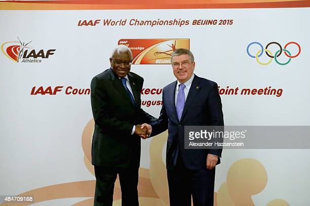 President Thomas Bach poses with IAAF President Lamine Diack after the media during a press conference after the IAAF Council and IOC Executive Board...