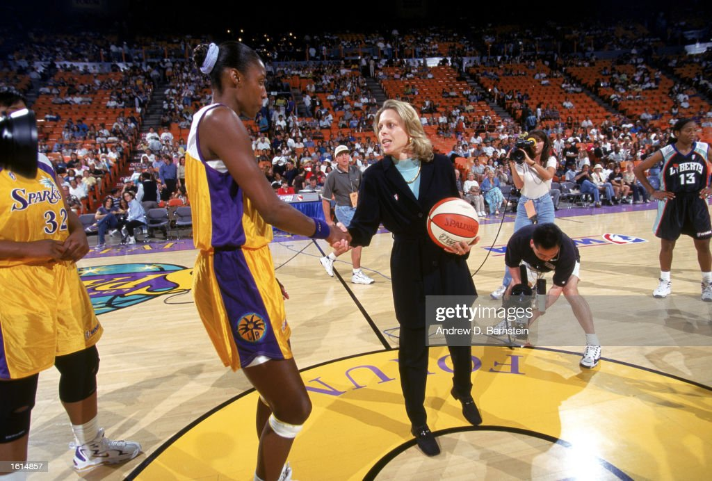 President Val Ackerman shakes hands with Lisa Leslie of the Los Angeles Sparks after the opening tip ceremony before the inaugural WNBA game against...