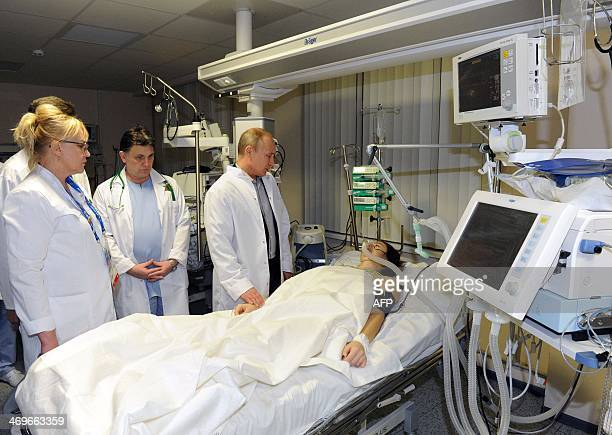 President Vladimir Putin visits Russian freestyle skier Maria Komissarova in a hospital in Sochi on February 15 2014 23yearold Maria Komissarova...