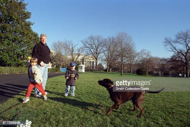 President William Jefferson Clinton and nephews Tyler Clinton and Zach Rodham playing with Buddy the Dog on the White House lawn December 25 1999...