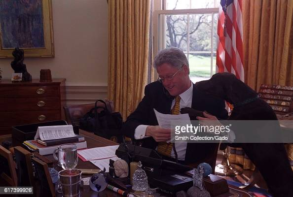 President William Jefferson Clinton sitting at his desk and on the phone with Russian President Boris Yeltsin Buddy the Dog resting head on his...