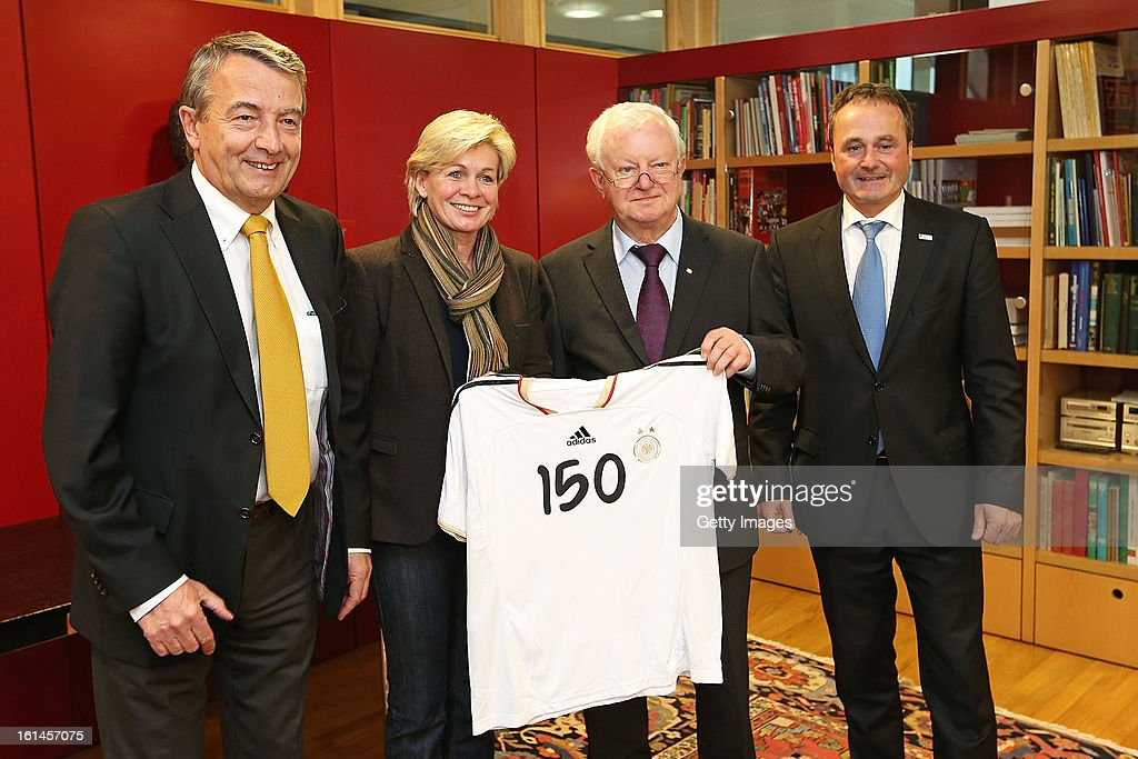 DFB president Wolfgang Niersbach, Silvia Neid, head coach of the German women's national football team, DRK president Dr. Rudolf Seiters, and Bernd Schmitz of the DRK are posing with a DFB jersey on February 11, 2013 in Frankfurt am Main, Germany.
