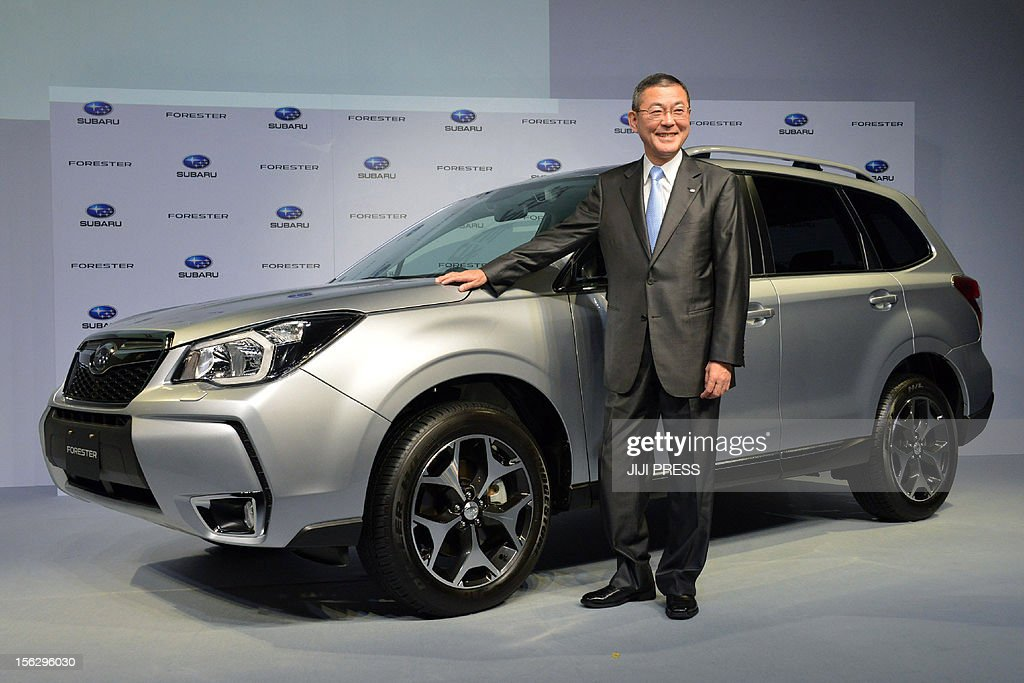 President Yasuyuki Yoshinaga of Japan's auto maker Fuji Heavy Industries known as Subaru displays the new SUV 'Forester' in Tokyo on November 13 2012...