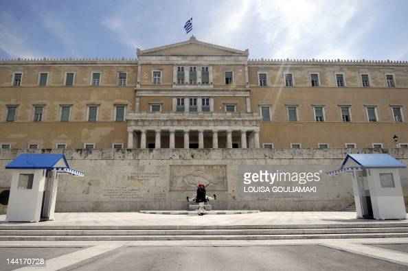 Presidental Evzoni guards march in front of the monument to the Unknown Soldier in front of the Greek Parliament in Athens on April 11 2012 Greek...