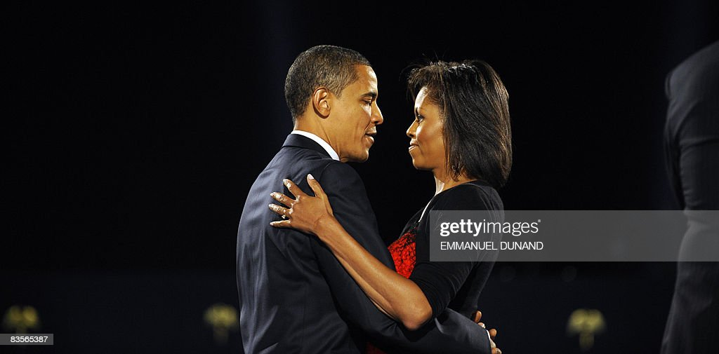 US presidentelect Barack Obama and his wife Michelle embrace on stage during Obama's election night victory rally at Grant Park on November 4 2008 in...