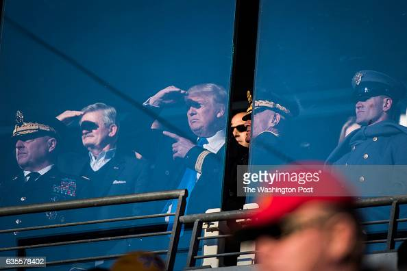PresidentElect Donald J Trump watches from a box with with US Army personnel and staff during an Army/Navy football game between the Navy Midshipmen...