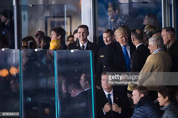 PresidentElect Donald J Trump watches from a box with with US Navy personnel and staff during an Army/Navy football game between the Navy Midshipmen...
