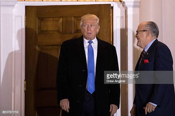 Presidentelect Donald Trump and former New York City mayor Rudy Giuliani exit the clubhouse following their meeting at Trump International Golf Club...