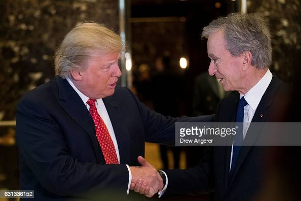 Presidentelect Donald Trump and French businessman Bernard Arnault chief executive officer of LVMH shake hands after speaking to reporters at Trump...