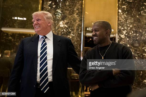 Presidentelect Donald Trump and Kanye West stand together in the lobby at Trump Tower December 13 2016 in New York City Presidentelect Donald Trump...