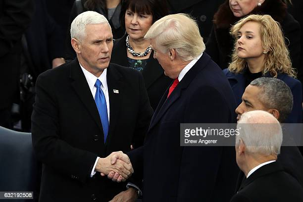 S Presidentelect Donald Trump and Vice Presidentelect Mike Pence shake hands on the West Front of the US Capitol on January 20 2017 in Washington DC...