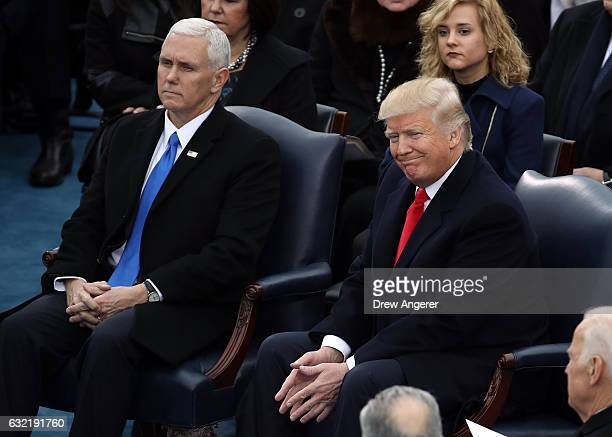 S Presidentelect Donald Trump and Vice Presidentelect Mike Pence watch speakers on the West Front of the US Capitol on January 20 2017 in Washington...