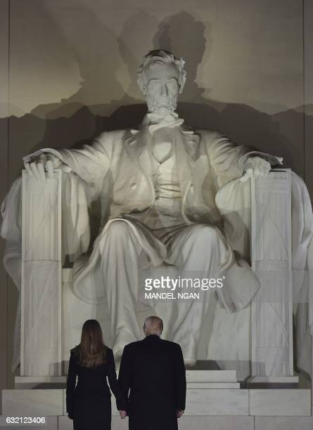 Presidentelect Donald Trump and wife Melania look at the Abraham Lincoln statue as they arrive for a welcome celebration at the Lincoln Memorial in...