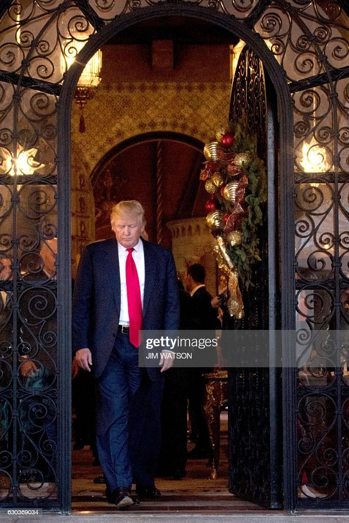 US President-elect Donald Trump exits Mar-a-Lago in Palm Beach, Florida, where he is taking meetings on December 21, 2016. / AFP / JIM