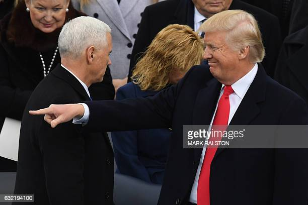 Presidentelect Donald Trump gestures after Mike Pence was sworn in as US Vice President on the platform at the US Capitol in Washington DC on January...