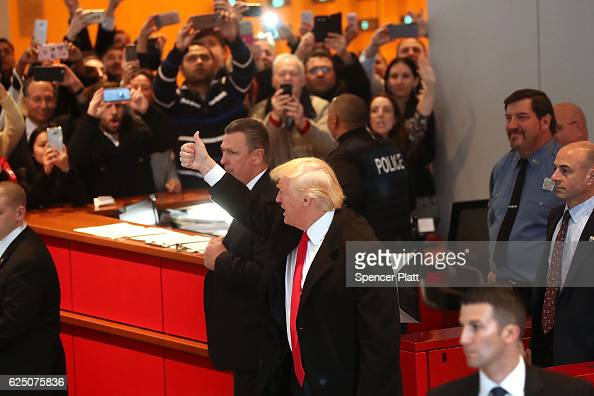 Presidentelect Donald Trump gives a thumbs up to the crowd as he walks through the lobby of the New York Times following a meeting with editors at...