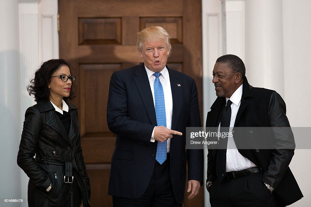 President-elect Donald Trump (C) greets Robert Johnson (R), the founder of Black Entertainment Television, and his wife Lauren Wooden (L) as they arrive for a meeting with president-elect Donald Trump at Trump International Golf Club, November 20, 2016 in Bedminster Township, New Jersey. Trump and his transition team are in the process of filling cabinet and other high level positions for the new administration.