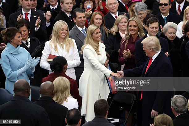 S Presidentelect Donald Trump is greeted by wife Melania Trump and daughters Tiffany Trump and Ivanka Trump on the West Front of the US Capitol on...