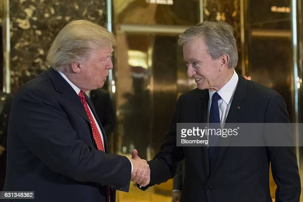 US Presidentelect Donald Trump left and Bernard Arnault chairman and chief executive officer of LVMH Moet Hennessy Louis Vuitton SA shake hands in...