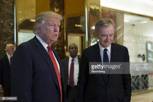 US Presidentelect Donald Trump left and Bernard Arnault chairman and chief executive officer of LVMH Moet Hennessy Louis Vuitton SA speak to members...