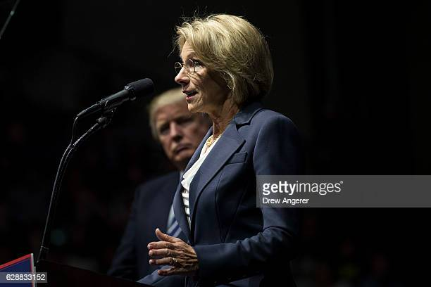 Presidentelect Donald Trump looks on as Betsy DeVos his nominee for Secretary of Education speaks at the DeltaPlex Arena December 9 2016 in Grand...