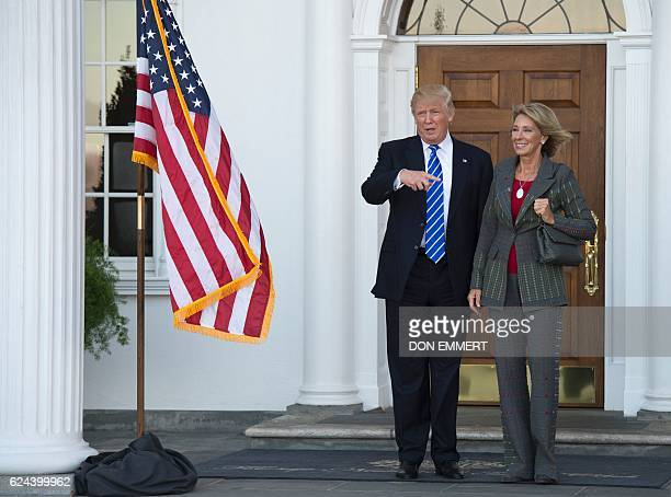 US Presidentelect Donald Trump poses for a photo with businesswoman Betsy DeVos on the steps of the clubhouse at Trump National Golf Club November 19...