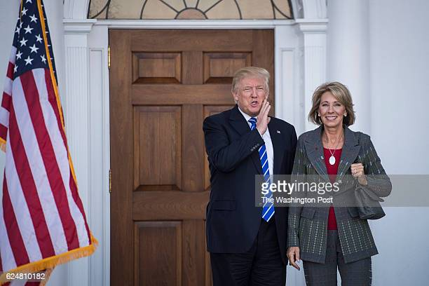 Presidentelect Donald Trump stands with Betsy DeVos after a meeting at Trump National Golf Club Bedminster in Bedminster Township NJ on Saturday Nov...
