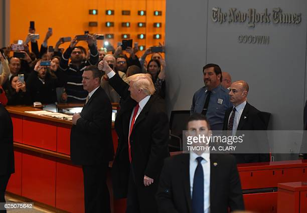 US Presidentelect Donald Trump waves to the crowd after leaving a meeting at the New York Times on November 22 2016 in New York US Presidentelect...