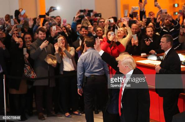 Presidentelect Donald Trump waves to the crowd as he walks through the lobby of the New York Times following a meeting with editors at the paper on...