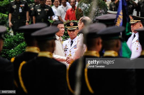 Presidentelect Rodrigo Roa Duterte and outgoing president Benigno Aquino III shake hands during the inauguration at Malacanang Palace on June 30 2016...
