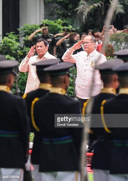 Presidentelect Rodrigo Roa Duterte and outgoing president Benigno Aquino III salute presidential honor guards during the inauguration at Malacanang...
