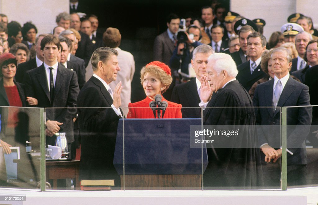 Presidentelect Ronald Reagan takes the oath of office during inauguration ceremonies in Washington DC His wife Nancy is holding the Bible and Chief...