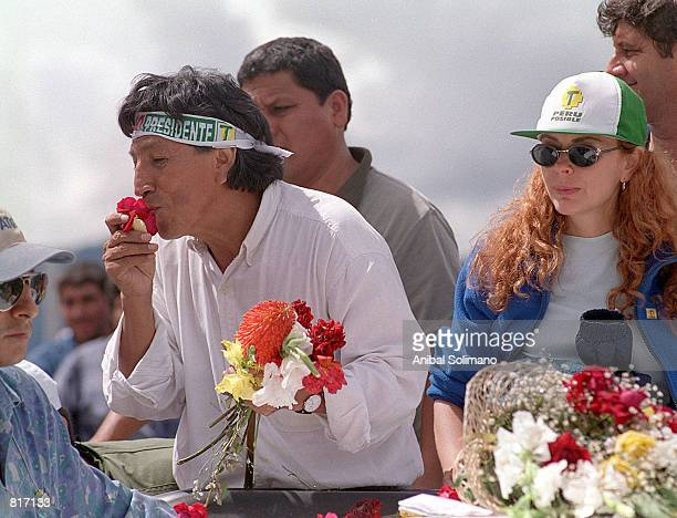 Presidential candidate Alejandro Toledo greets supporters as he kisses a flower upon entering the Andean town of Huaraz as his wife Eliane right and...