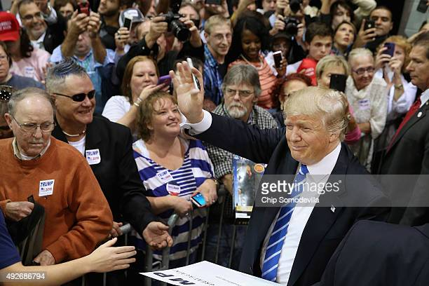 Presidential candidate and Republican frontrunner Donald Trump shakes hands and gives autographs during a campaign rally at the Richmond...