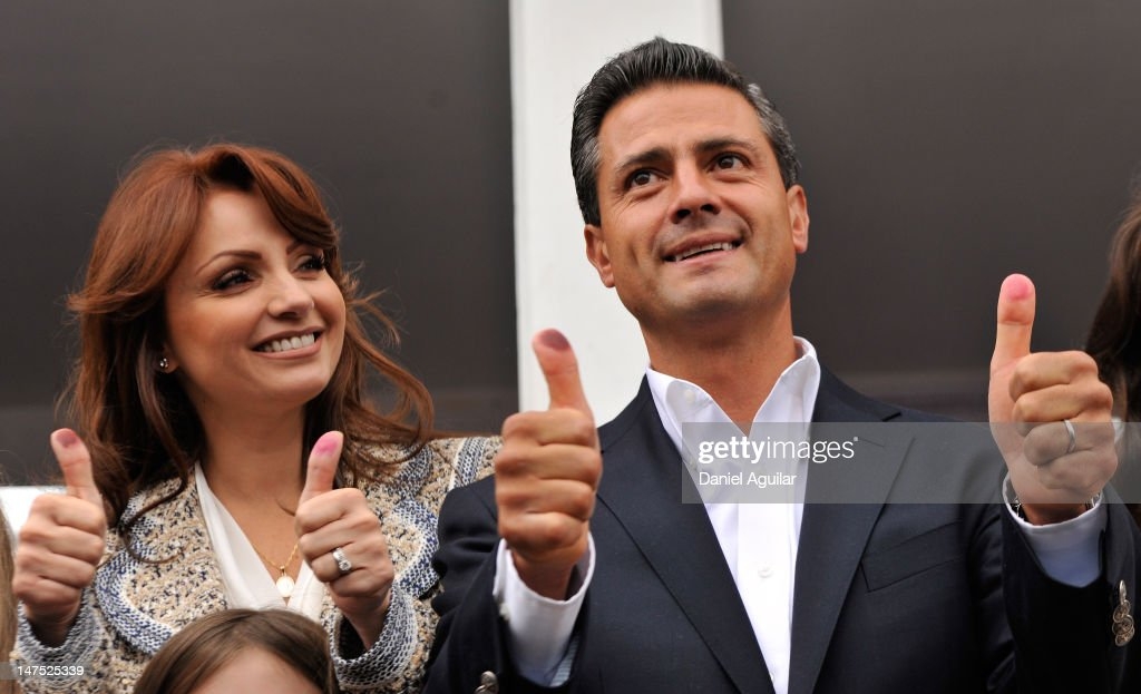 Presidential candidate Enrique Pena Nieto of the Institutional Revolutionary Party (PRI), gesutres as he casts his vote with his wife Angelica Rivero de Pena on July 1, 2012 in Atlacomulco, Mexico. Mexicans went to the polls to choose a new president and vote in thousands of state and local posts nationwide.