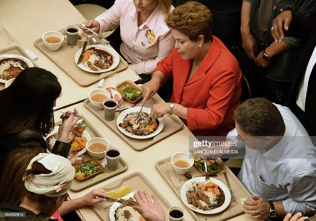 Presidential candidate for the Brazilian Workers' Party and current Brazilian President Dilma Rousseff (C-in red), has lunch at a the 'Presidente Getulio Vargas' budget restaurant in Bangu, western Rio de Janeiro, Brazil on August 27, 2014. The restaurant serves a meal for 1.00 real (USD 50 cents).