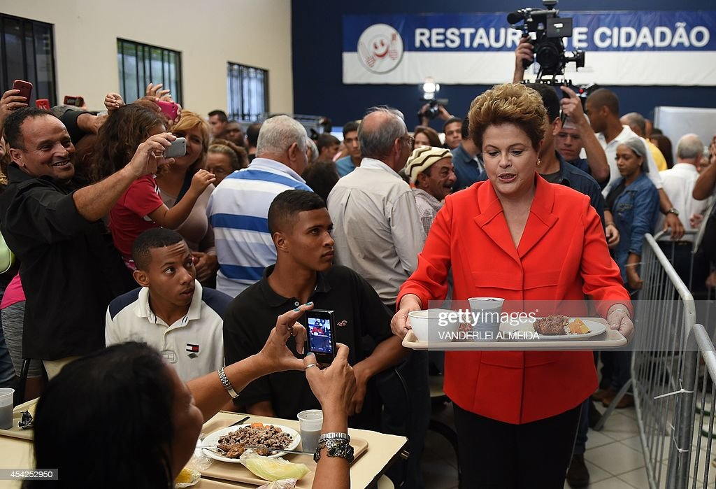 Presidential candidate for the Brazilian Workers' Party and current Brazilian President Dilma Rousseff (R), has lunch at a the 'Presidente Getulio Vargas' budget restaurant in Bangu, western Rio de Janeiro, Brazil on August 27, 2014. The restaurant serves a meal for 1.00 real (USD 50 cents).