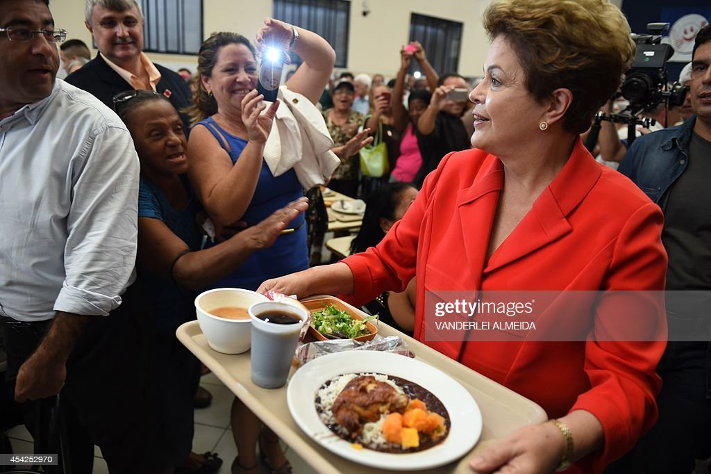 Presidential candidate for the Brazilian Workers' Party and current Brazilian President Dilma Rousseff (R), has lunch at a the 'Presidente Getulio Vargas'budget restaurant in Bangu, western Rio de Janeiro, Brazil on August 27, 2014. The restaurant serves a meal for 1.00 real (USD 50 cents).