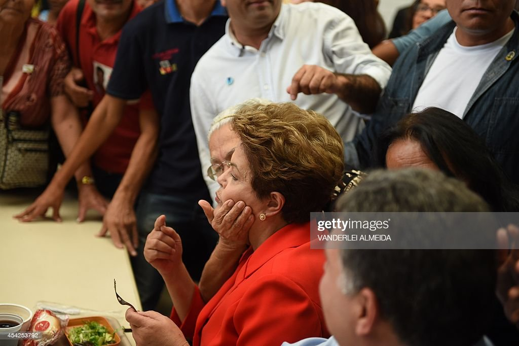 Presidential candidate for the Brazilian Workers' Party and current Brazilian President Dilma Rousseff (C), is greeted by a supporter whilst having lunch at a the 'Presidente Getulio Vargas' budget restaurant in Bangu, western Rio de Janeiro, Brazil on August 27, 2014. The restaurant serves a meal for 1.00 real (USD 50 cents).