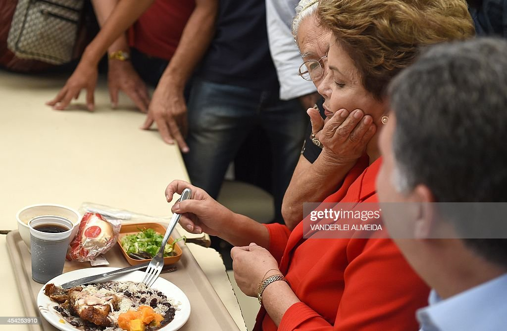 Presidential candidate for the Brazilian Workers' Party and current Brazilian President Dilma Rousseff (R), is greeted by a supporter whilst having lunch at a the 'Presidente Getulio Vargas' budget restaurant in Bangu, western Rio de Janeiro, Brazil on August 27, 2014. The restaurant serves a meal for 1.00 real (USD 50 cents).