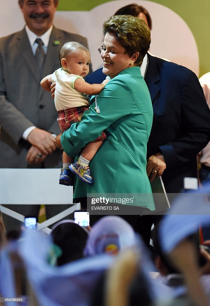 Presidential candidate for the Brazilian Workers' Party and current Brazilian President Dilma Rousseff (L) holds a child during a rally at National Confederation of Rural Workers (CONTAG) in Brasilia, Brazil on August 28, 2014. Rousseff is set for a bruising defeat in an October runoff election against popular environmentalist Marina Silva, a poll suggested Tuesday. The survey by polling firm Ibope found Rousseff would come out ahead in the first-round election on October 5 but be forced to face Silva in a second-round vote three weeks later, losing 36 percent to 45 percent. AFP PHOTO/EVARISTO SA