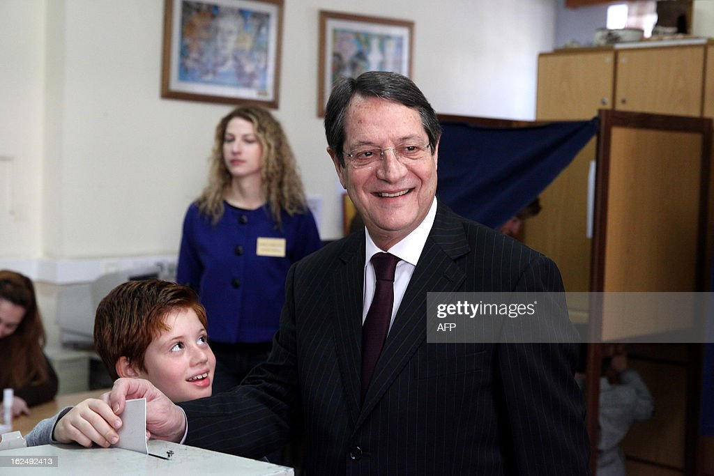 Presidential candidate for the Democratic Rally of Cyprus (DISY) party, Nicos Anastasiades casts his ballot near his grandson during the second round of Cyprus' presidential election on February 24, 2013 in Limassol. Cypriots began voting in a crucial left-right presidential runoff to elect a new leader to seal a much needed rescue package for the EU state on the brink of financial ruin.