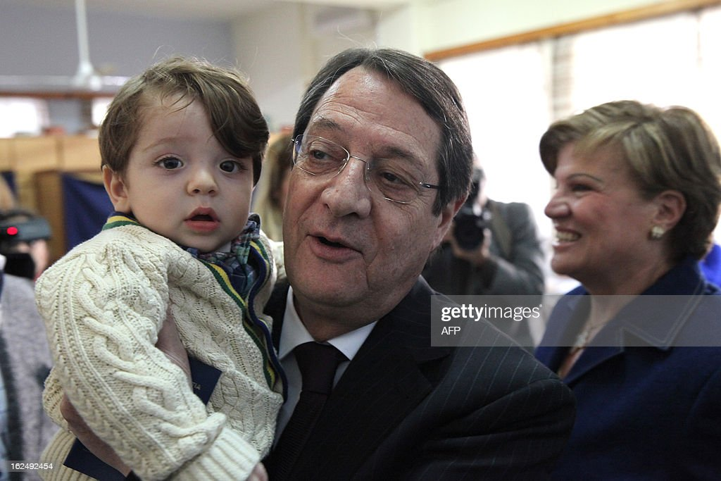 Presidential candidate for the Democratic Rally of Cyprus (DISY) party, Nicos Anastasiades holds his grandson as he leaves the polling station after voting in the second round of Cyprus' presidential election on February 24, 2013 in Limassol. Cypriots began voting in a crucial left-right presidential runoff to elect a new leader to seal a much needed rescue package for the EU state on the brink of financial ruin.